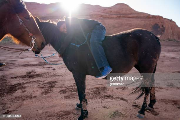 a young native american boy putting his arms around his horse - apache stock pictures, royalty-free photos & images