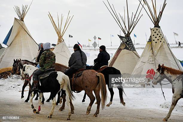 Young native american horsemen take their horses for a ride through Oceti Sakowin Camp on the edge of the Standing Rock Sioux Reservation on December...