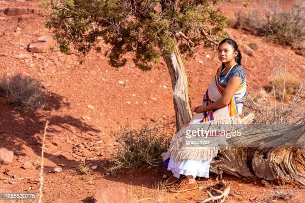 une jeune fille amérindienne et navajo rectifiée dans sa belle robe traditionnelle, se reposant sur une vieille souche à côté d'un chêne de gommage - apache photos et images de collection