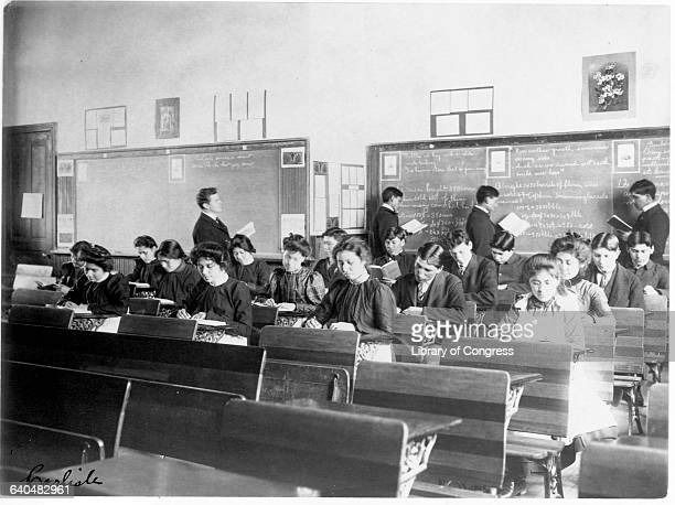 Young Native American students writing at their desks and standing at the chalkboard during class at the Carlisle Indian School Carlisle Pennsylvania...