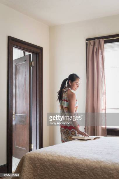 young native american woman in her bedroom with book - idaho falls stock photos and pictures