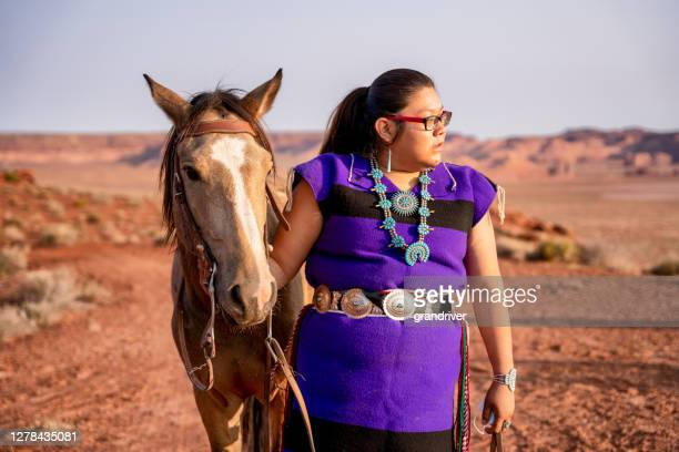 young native american woman in her twenties looking into the distance and holdiing the bridal of her horse - apache stock pictures, royalty-free photos & images