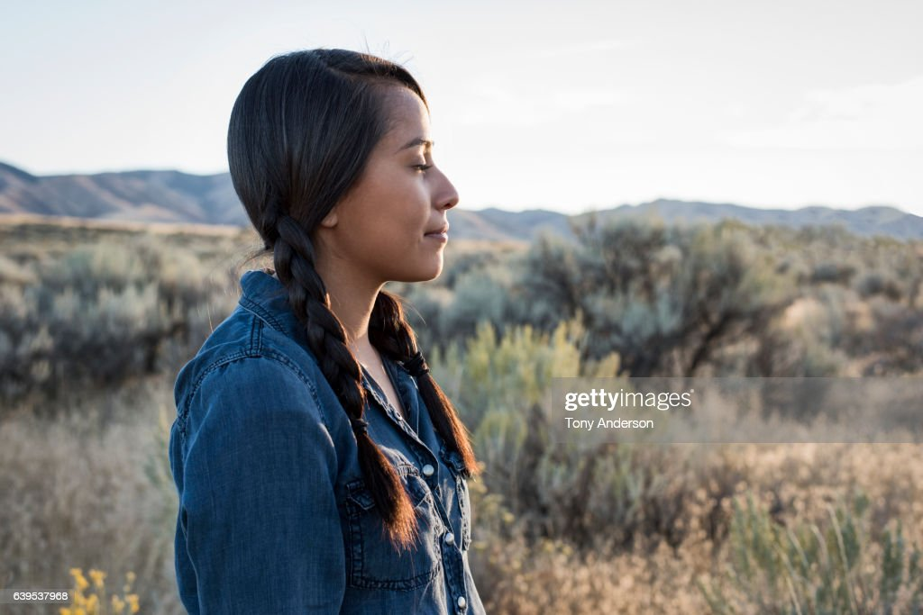 Young Native American woman outdoors at sunset : Stock Photo