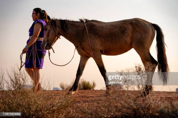 a young native american woman wearing her native dress and turquoise jewelry walking with her horse, the monument valley in the background - cherokee culture stock pictures, royalty-free photos & images