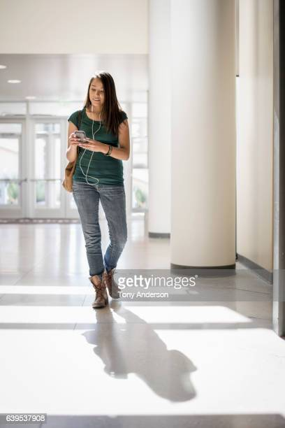 Young Native American woman with phone in public building