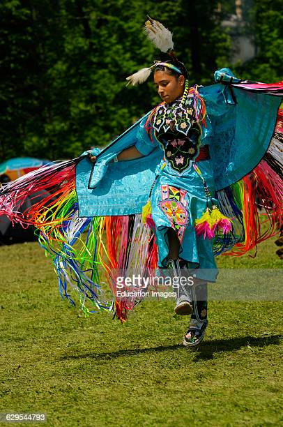 Young Native Indian girl airborne in the Fancy Shawl Dance competition at the Grand River Pow Wow