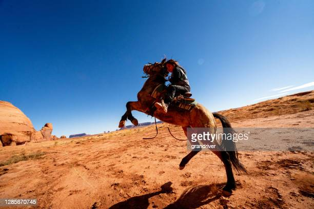a young navajo boy riding, his horse bucking on the desert plain in monument valley, arizona, monument valley tribal park - apache stock pictures, royalty-free photos & images