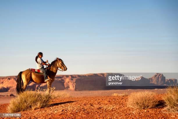 un jeune garçon navajo avec son cheval, équitation ludique sur un plateau au-dessus de sa maison, avec la vallée de monument derrière lui - apache photos et images de collection