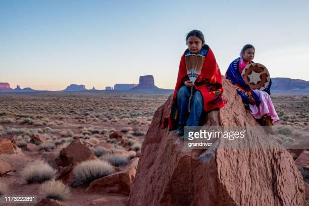 jeune frère et soeur de navajo dans la vallée de monument posant sur des roches rouges devant les formations rocheuses étonnantes de mittens dans le désert à l'aube - apache photos et images de collection