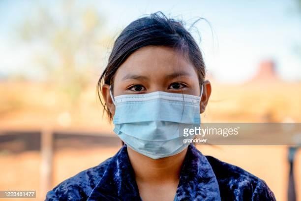 uma jovem navajo usando uma máscara protegendo-a de covid19, com monument valley atrás dela - cultura indígena - fotografias e filmes do acervo