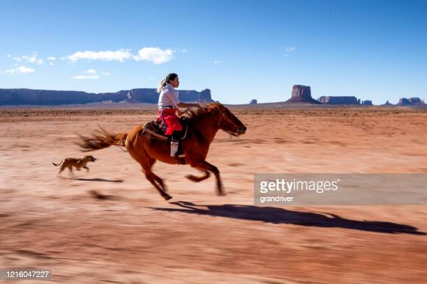a young navajo riding her horse fast as the dogs chase after her - native american reservation stock pictures, royalty-free photos & images