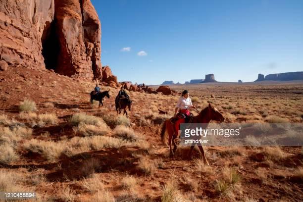 モニュメントバレーの家族の土地に馬に乗っている若いナバホ兄弟 - ナバホ文化 ストックフォトと画像