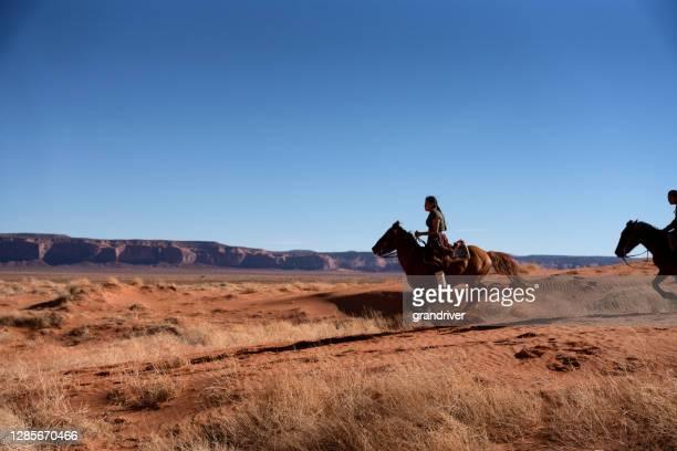 jeunes frères et sœurs navajos conduisant leurs chevaux avec la vallée de monument à l'arrière-plan - apache photos et images de collection
