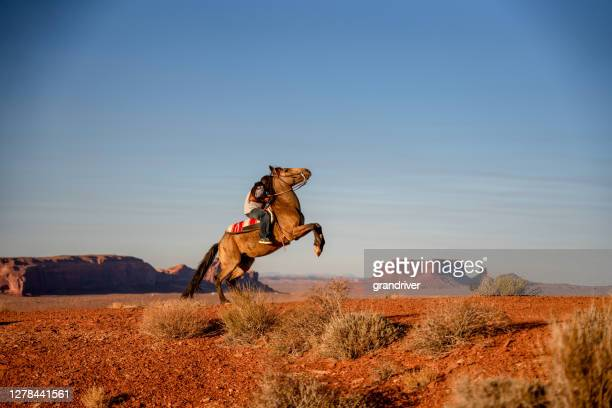young navajo teenage boy expertly riding his horse making it buck in the desert in the northern arizona navajo reservation in monument valley tribal park - cherokee culture stock pictures, royalty-free photos & images