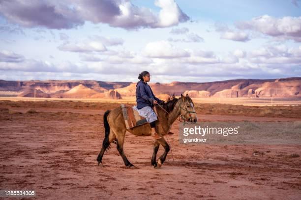 une jeune adolescente navajo conduisant, son cheval sur la plaine de désert près de butte de chameau dans la vallée de monument, arizona, parc tribal de vallée de monument - apache photos et images de collection