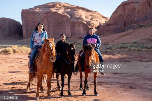 young navajo teenage siblings on their horses with a rock formation behind them - native american reservation stock pictures, royalty-free photos & images