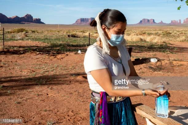 コロナウイルスから彼女を守るために手の消毒剤を適用する若いナバホティーンエイジャー - ナバホ文化 ストックフォトと画像