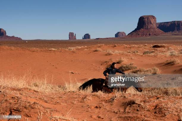 a young navajo woman dressed in traditional clothing riding her horse across the desert near camel butte, monument valley, arizona - apache stock pictures, royalty-free photos & images
