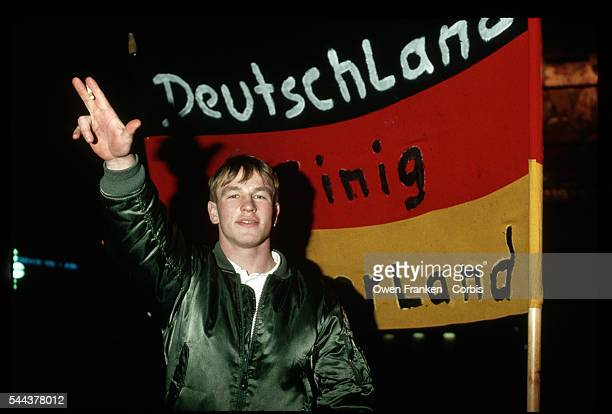 Young neo-Nazi salutes as he stands in front of a banner at a night rally in Leipzig, East Germany.