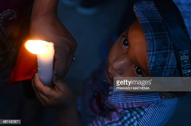 A young Nepalese boy holds a candle in memory of the 16 Nepalese Sherpa guides killed in an avalanche on Mount Everest in Katmandu on April 30 2014...