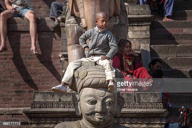 A young Nepalese boy sits on a statue while waiting for the beginning of the first day of the Bisket Jatra festival on April 10 2015 in Bhaktapur...
