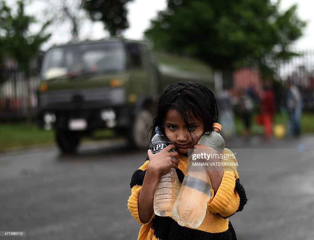 A young Nepalese girl carries drinking water to her make-shift tent in Kathmandu on April 30, 2015, following a 7.8 magnitude earthquake which struck the Himalayan nation on April 25. The UN launched an appeal for Nepalese quake survivors in dire need of shelter, food and medical care April 30, as anger boiled at the government's inability to cope with a disaster that has killed more than 5,000 people.