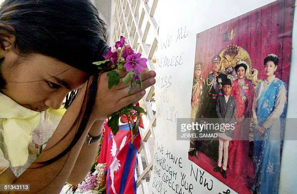 A young Nepalese girl prays in front of a portrait of royal family members including the late King Birendra Queen Aishwariya and late King Dipendra...