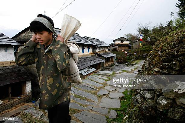 Young Nepalese man carries a heavy load in the mountain village of Dhampus on March 16, 2007 in Nepal. The village is home to many Gurung who are the...