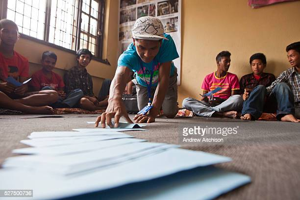 A young Nepalese man leans forward to collect an activity card during a life skills training session in Bisaneu Voice of Children centre in Kathmandu...