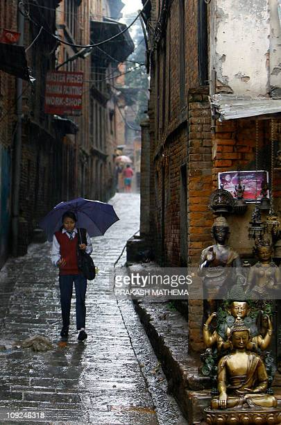 A young Nepalese woman walks down a narrow street during a downpour in Bhaktapur some 12kms southeast of Kathmandu on February 16 2011 Bhaktapur is...