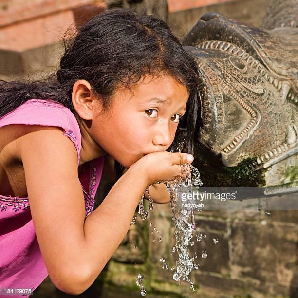 Junge Nepali Mädchen trinken aus Brunnen in city Durbar Square