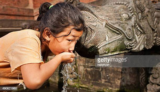 Young Nepali girl drinking from city fountain on Durbar Square