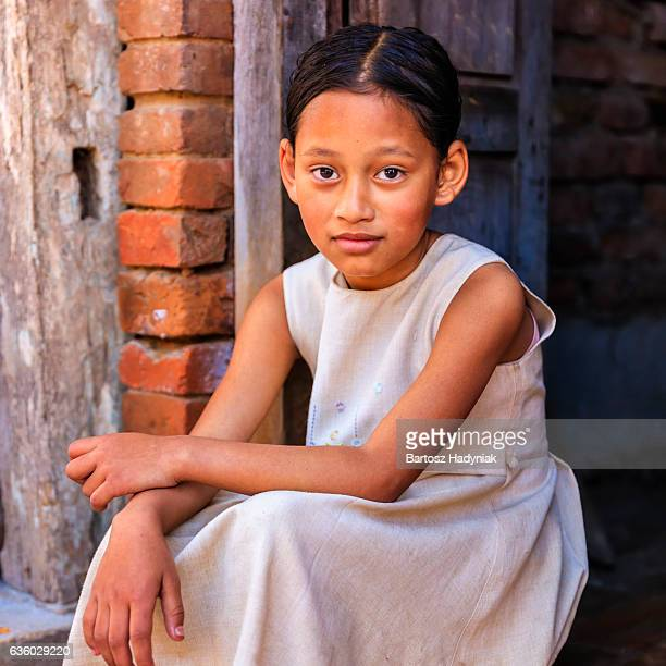 Young Nepali girl sitting outside her house in Bhaktapur, Nepal