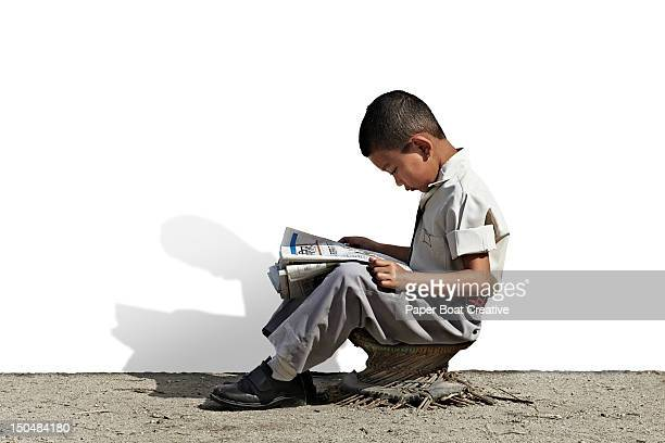 young nepali school boy reading newspaper - nepal stock pictures, royalty-free photos & images