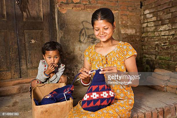 young nepali woman knitting wool hat in bhaktapur - nepal stock pictures, royalty-free photos & images