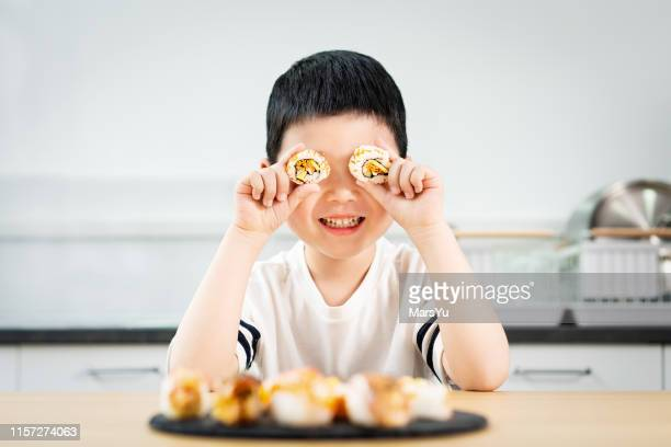 young nerd boy eating sushi - japanese food stock pictures, royalty-free photos & images