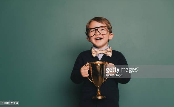 young nerd boy holding first place trophy - vincere foto e immagini stock