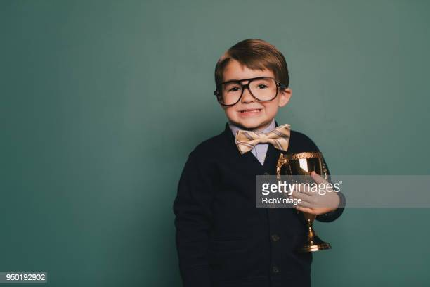 young nerd boy holding trophy - spelling stock pictures, royalty-free photos & images