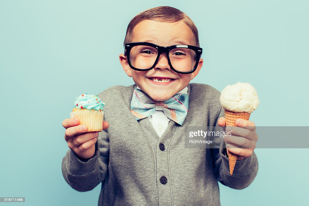 Young Nerd Boy Holds Ice Cream and Cupcakes : Stock Photo