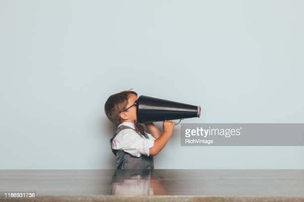 young nerd boy with megaphone - wrong way stock pictures, royalty-free photos & images