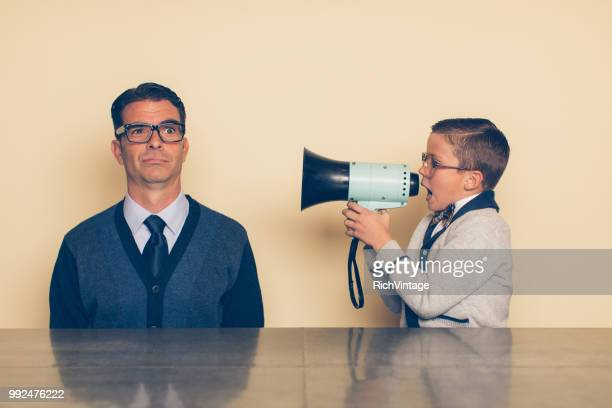 young nerd boy yelling at dad through megaphone - crazy dad stock photos and pictures