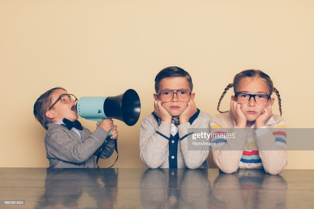 Young Nerd Boy Yelling at Siblings with Megaphone : Stock Photo