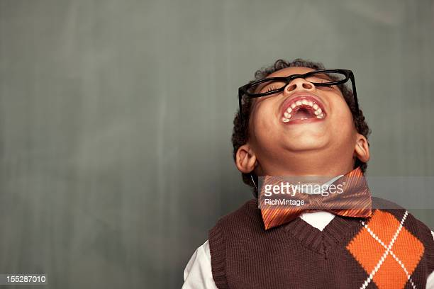 Young nerd in glasses leaning back and laughing