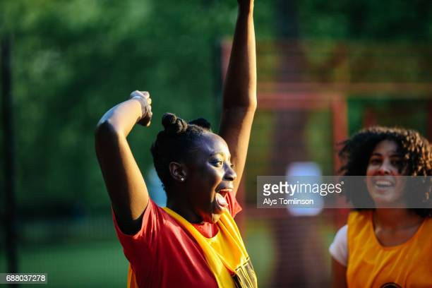 young netball player celebrating win on netball court - leanincollection stock pictures, royalty-free photos & images