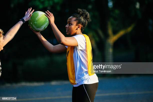 young netball player holding ball and being marked during netball match on outdoor court