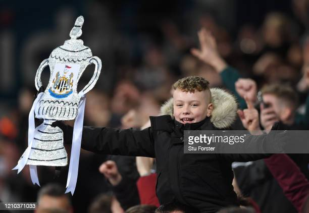 A young Newcastle fan celebrates victory with a canny homemade tin foil FA cup after the FA Cup Fifth Round match between West Bromwich Albion and...