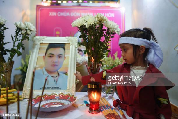 A young niece of Hoang Van Tiep holds his portrait on a coffin bearing his remains during a funeral in Dien Chau district Nghe An province on...