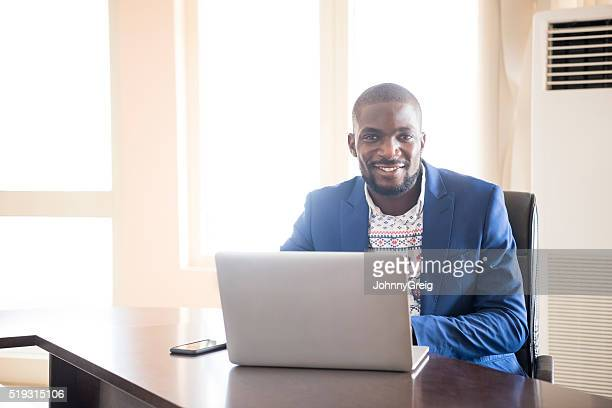 Young Nigerian businessman in office using laptop
