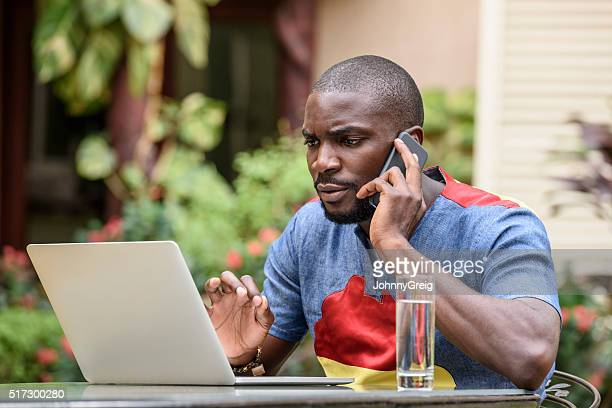Young Nigerian businessman on cell phone with laptop