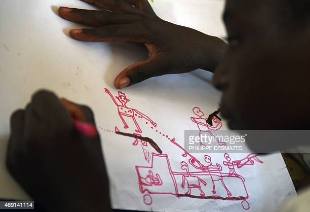 A young Nigerian refugee draws an attack scene on April 6 2015 during a therapy program managed by UNICEF in the refugee camp near Baga Sola Seven...